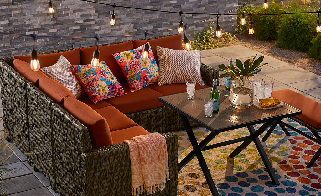 Wicker sectional sofa with red cushions with a coffee table on a patio.