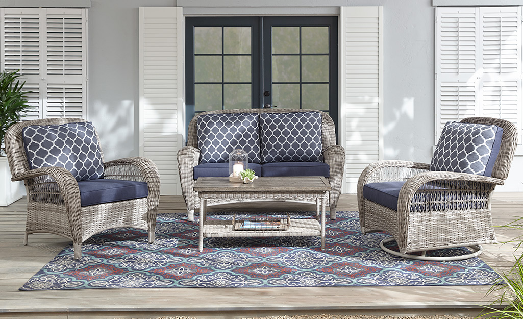 Wicker lounge chairs, love seat and coffee table on a large patio.