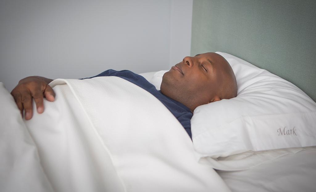 Một người đàn ông đang ngủ trên lưng của mình.