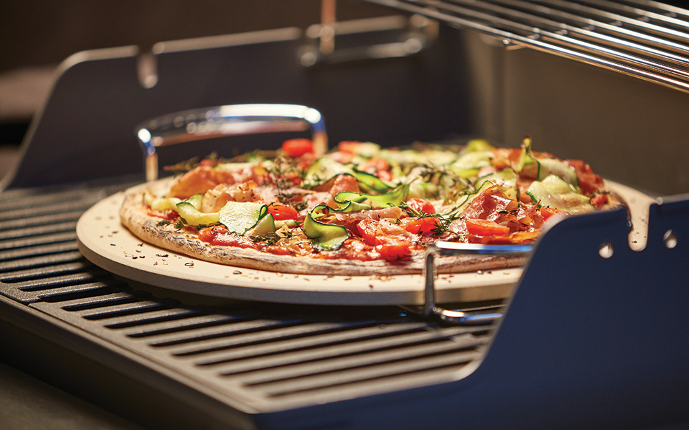 A pizza sits on a pizza stone on a grill.