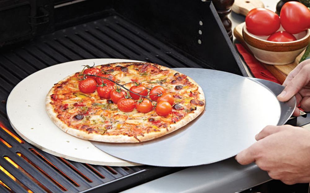 A person using a pizza peel to lift a pizza from a grill.