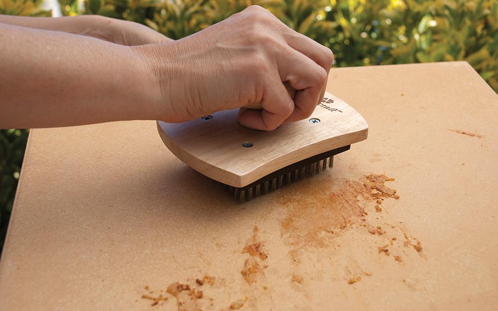 A person scrubbing a pizza stone with a brush.