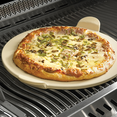 A pizza with mushrooms and green peppers sits on a pizza stone in a grill.