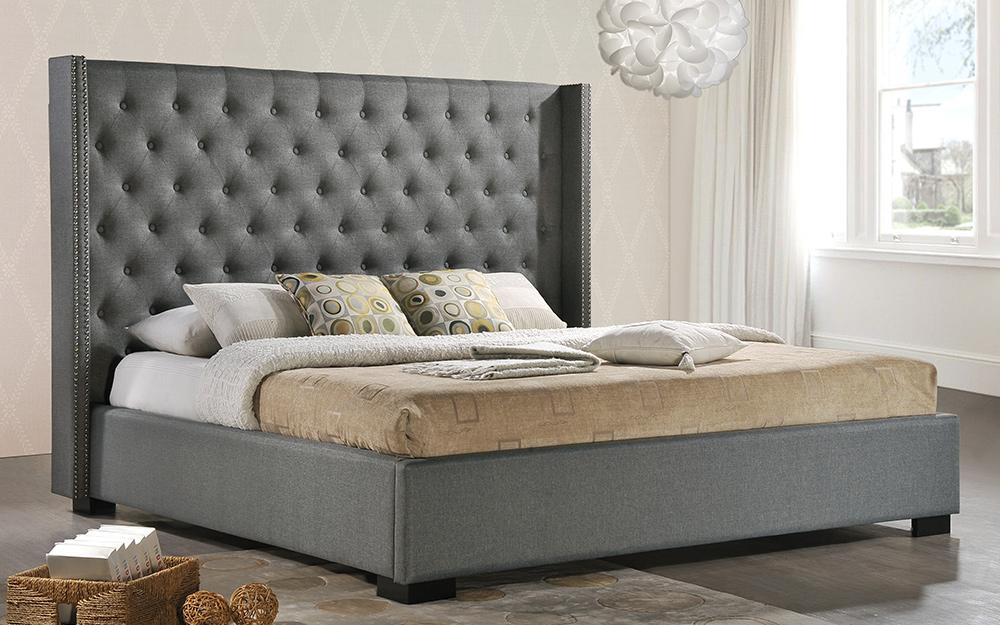 giường nền với đầu giường bọc nệm màu xám.