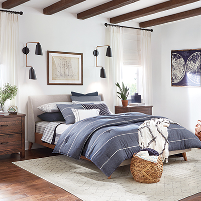 A platform bed with a blue comforter in a bedroom.