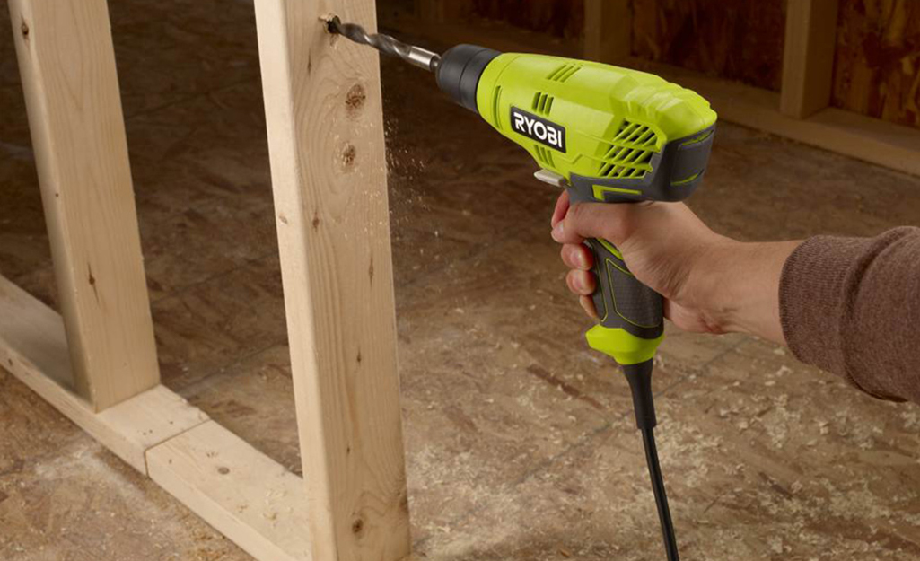 A person using a corded Ryobi drill on a wooden frame.