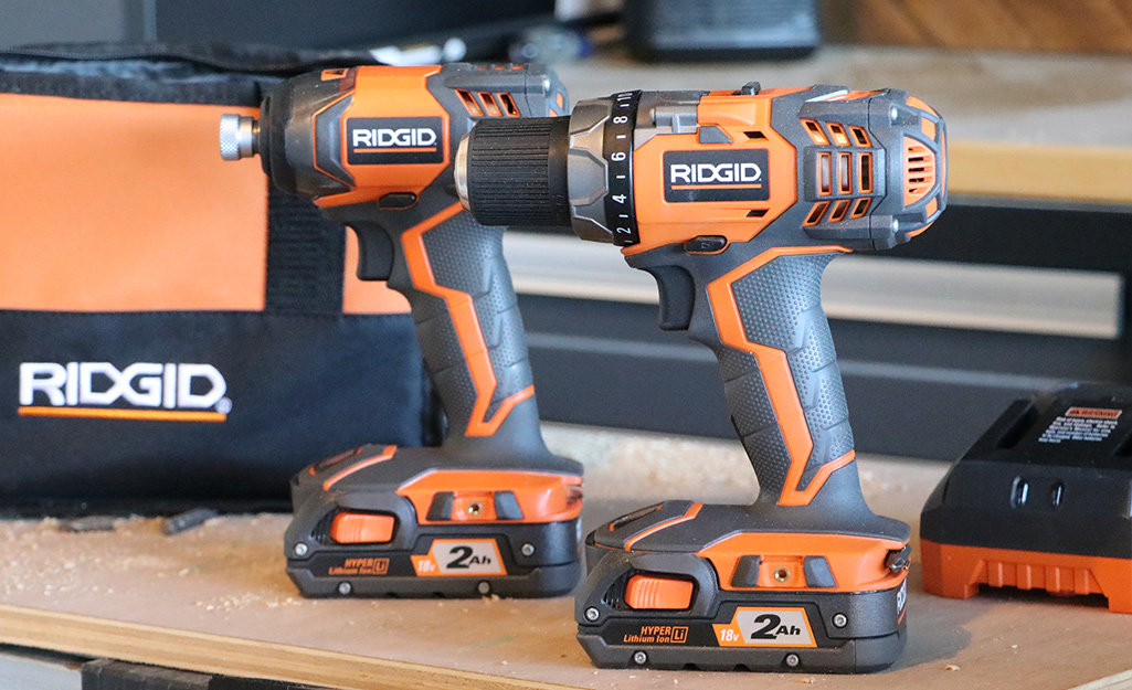 Two power drills side by side on a wooden table.