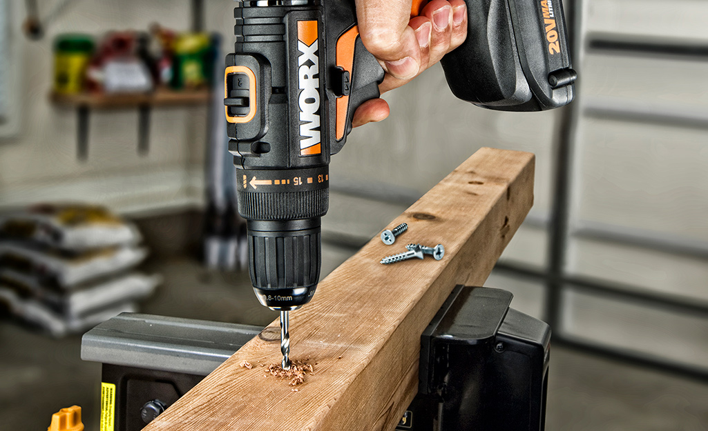 A person drilling into a wood beam with a power drill.