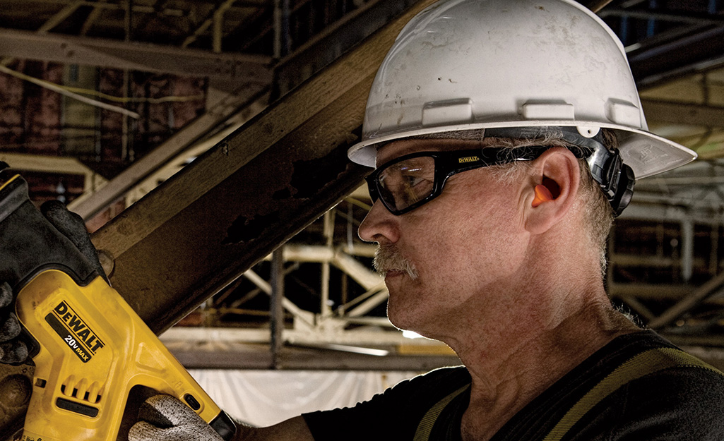 A man wearing safety glasses and a hard hat while using a power tool.