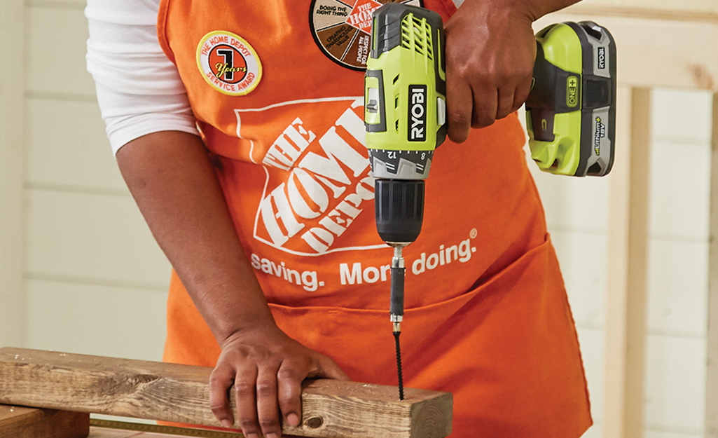 A person in a home Depot apron using a Ryobi power drill.