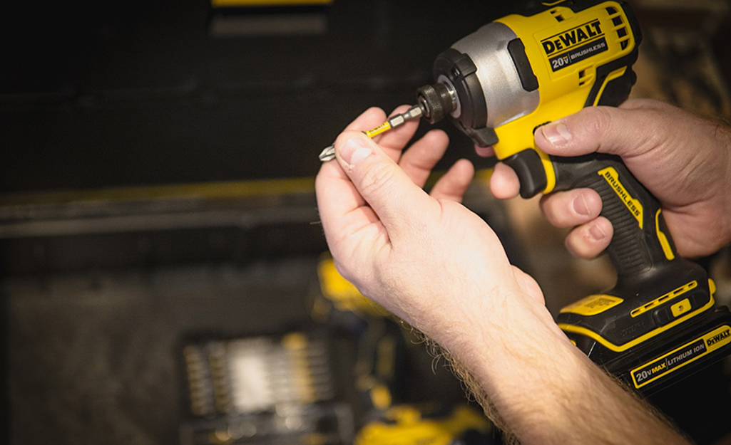 A person changing out the drill bit on a power drill.