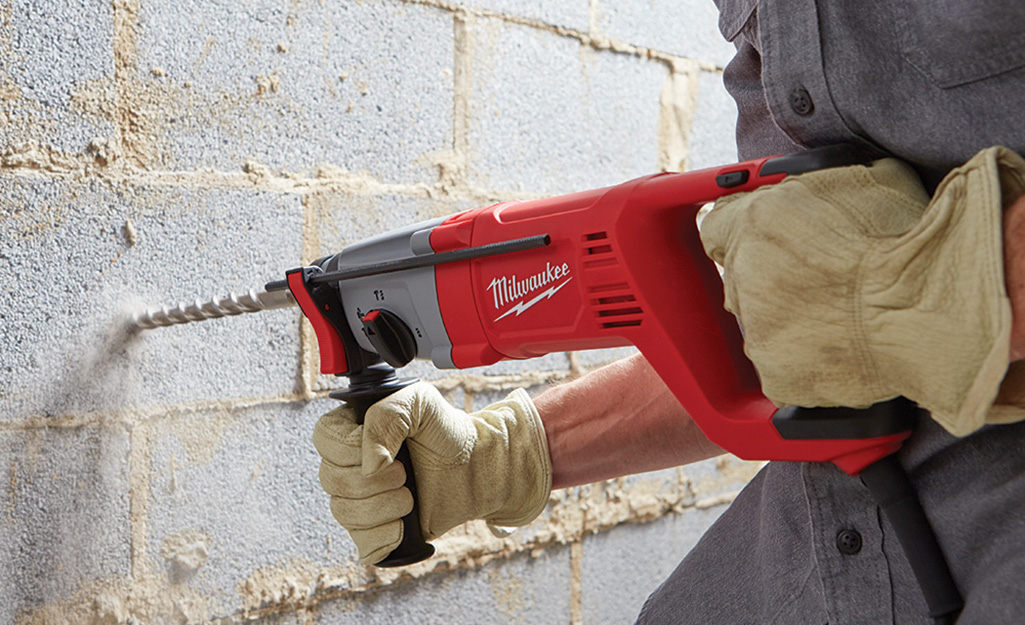 A person using a hammer drill to drill a concrete wall.
