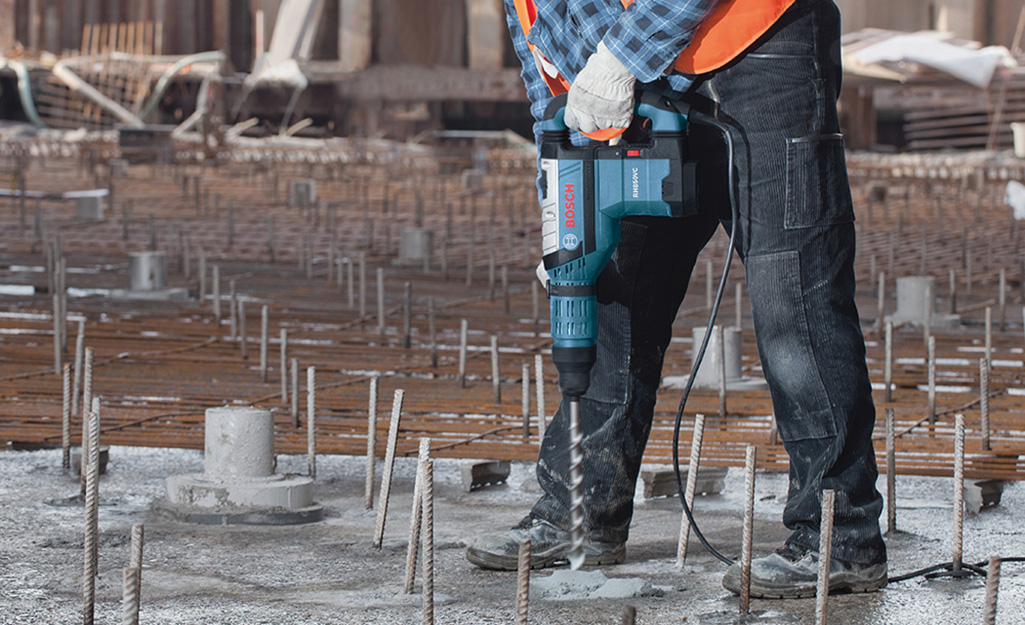 A person using a rotary hammer drill to set into a foundation.