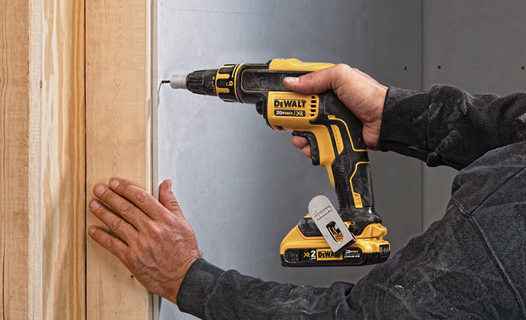 A person using a screw gun on a wooden frame against a wall.