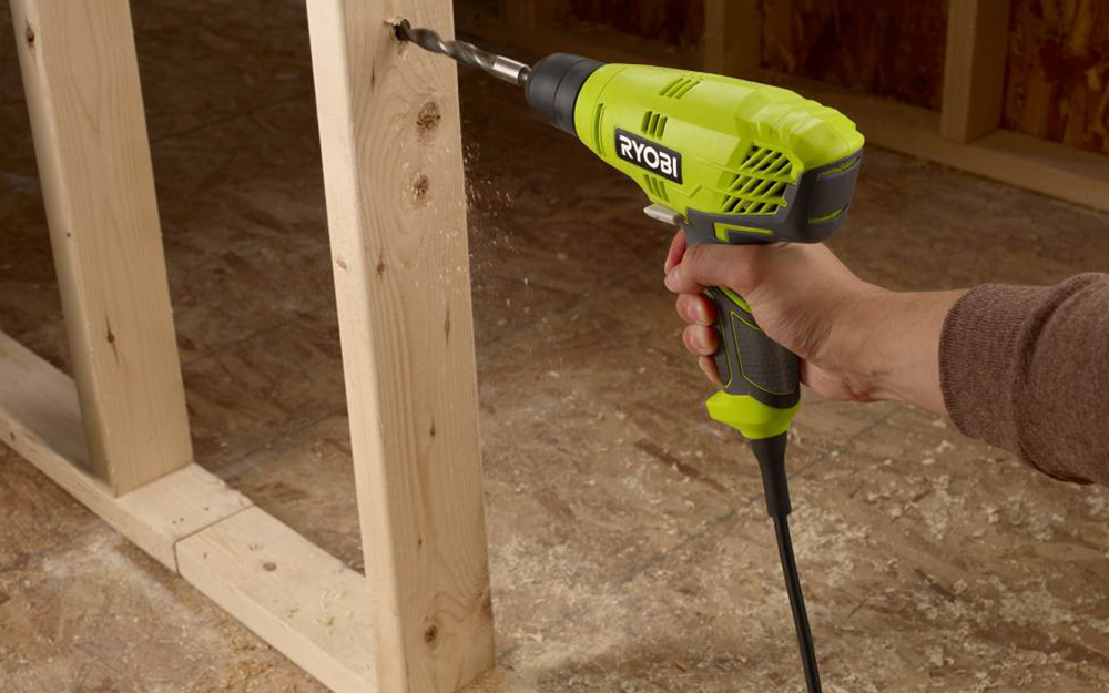 person using a corded Ryobi drill on a wooden frame