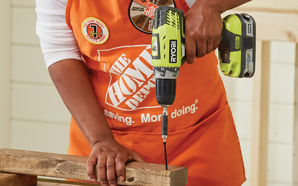 person in a home Depot apron using a Ryobi power drill
