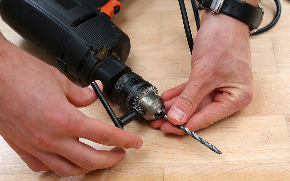 person changing out the drill bit on a power drill