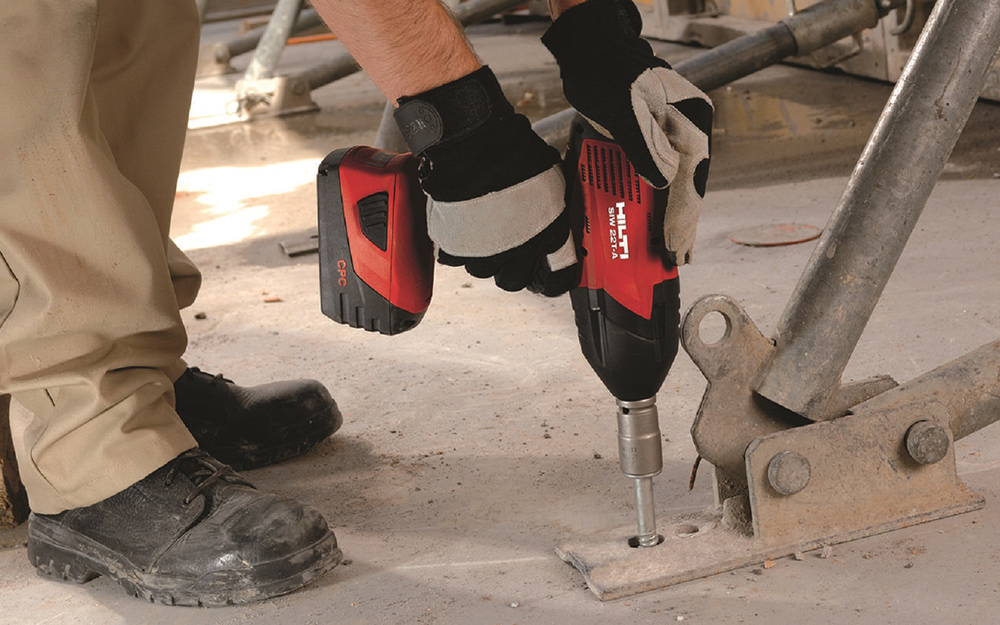 person using a power drill with a spade drill bit
