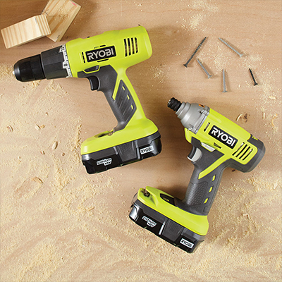 Two cordless Ryobi drills with screws on a wooden panel