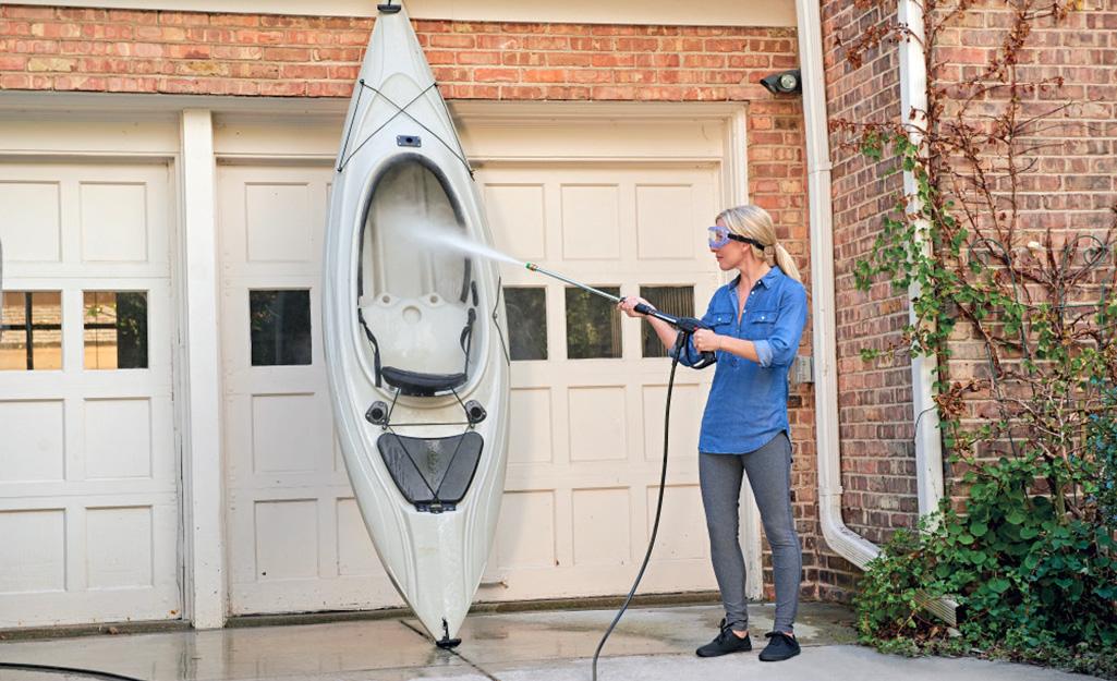 Woman using a pressure washer on a fiberglass canoe.