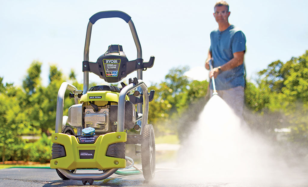 A man uses pressure washer to clean outside.