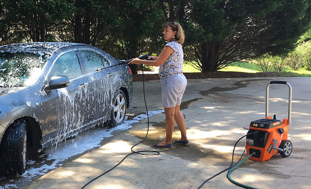 A woman pressure washing a car.