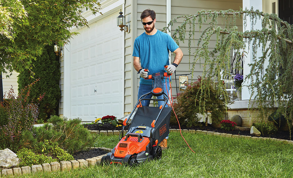 A man uses a push mower in his front yard.