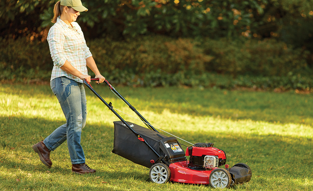 A woman uses a gas push mower.