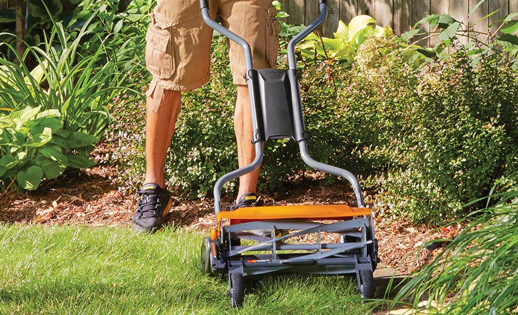 A man using a reel mower.