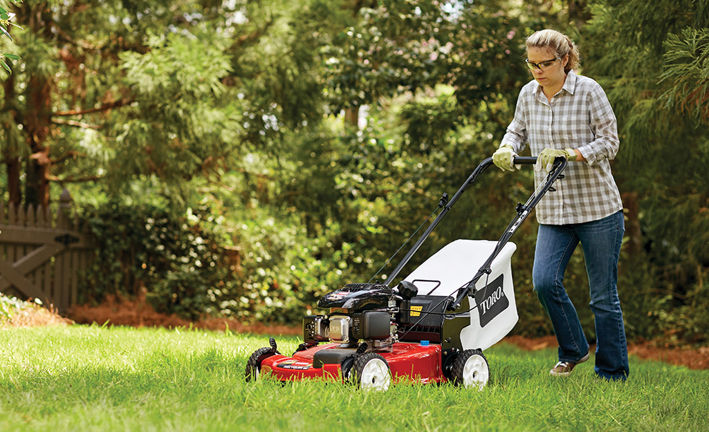 A woman is mowing a sloped lawn with a push mower.