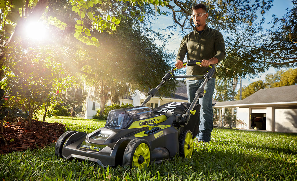A man uses a push mower on large, healthy front lawn.