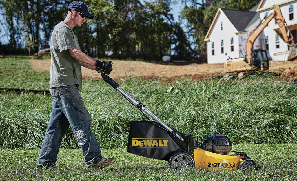 A man uses a push mower that automatically collects clippings.