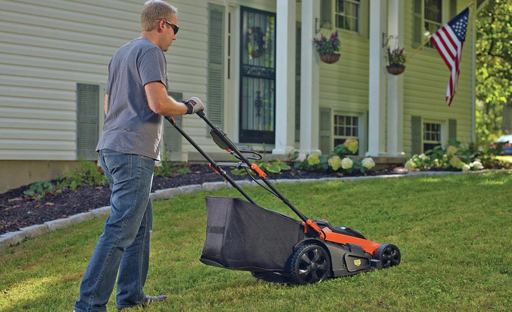 A man uses a high-wheel push mower.