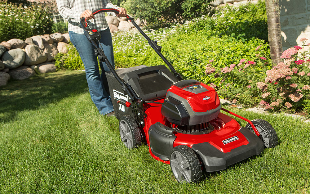 Person is pushing a mower in a yard.