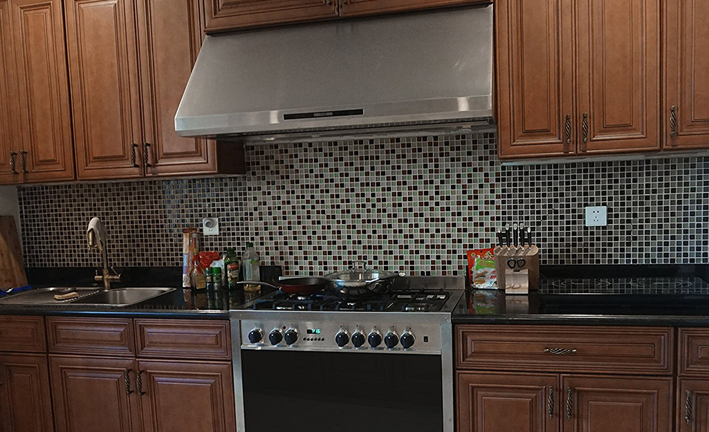 A stainless steel under-the-cabinet range hood installed in a kitchen with wooden cabinets.