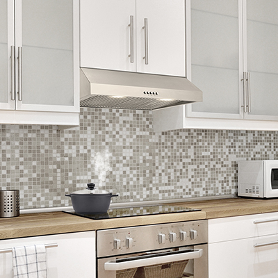 A stainless steel under-the-cabinet range hood in a kitchen with a tile backsplash.
