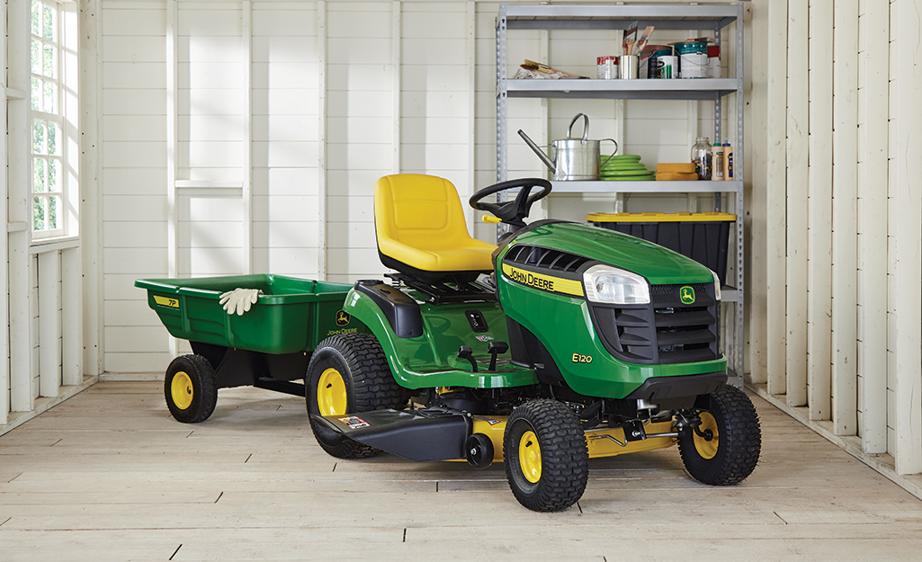 A green and yellow riding mower inside a garage.