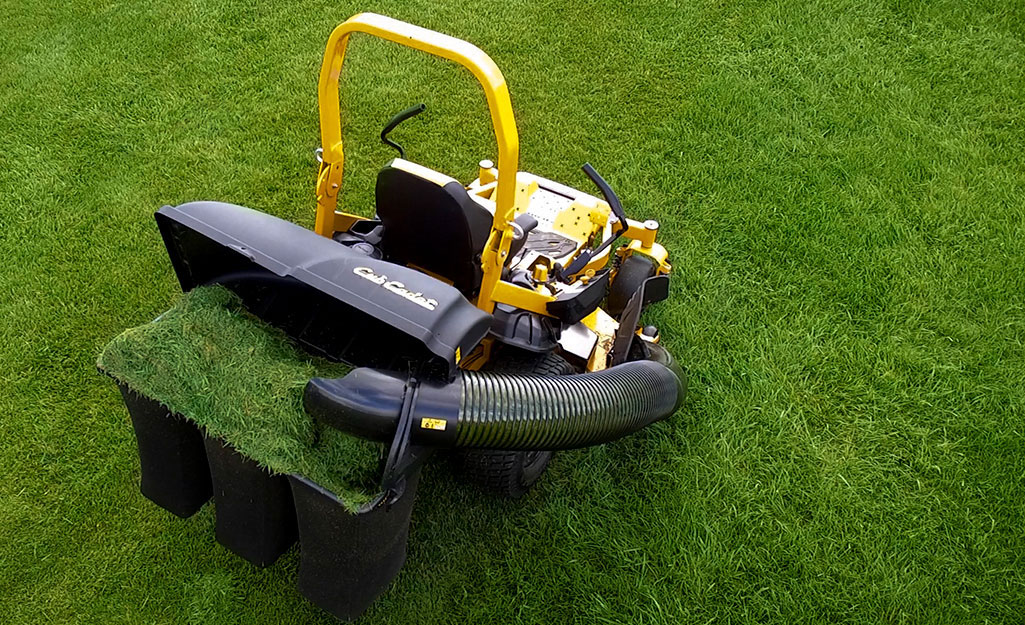 A lawn mower attachment helps bag lawn clippings.