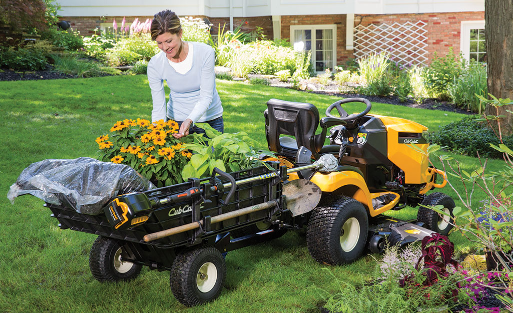 A woman taking flowers out of her mower's tractor attachment.