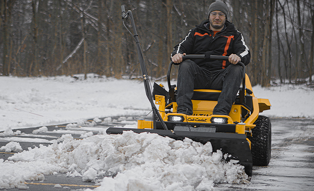 A man uses a garden mower in the snow.