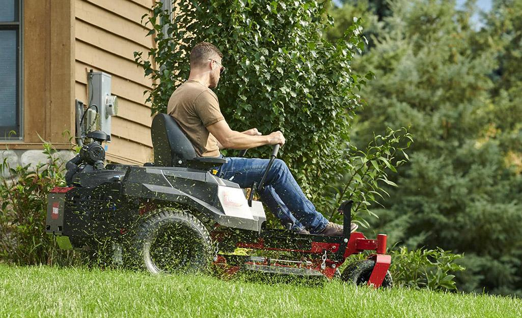 A man uses a zero-turn radius mower.