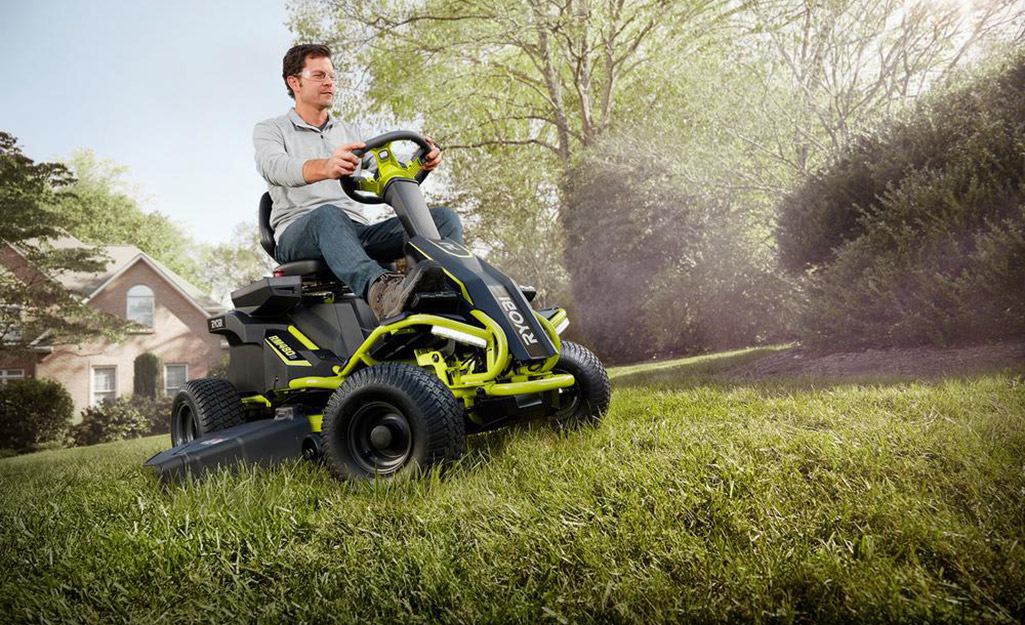 A man riding a mower with rear engine power.