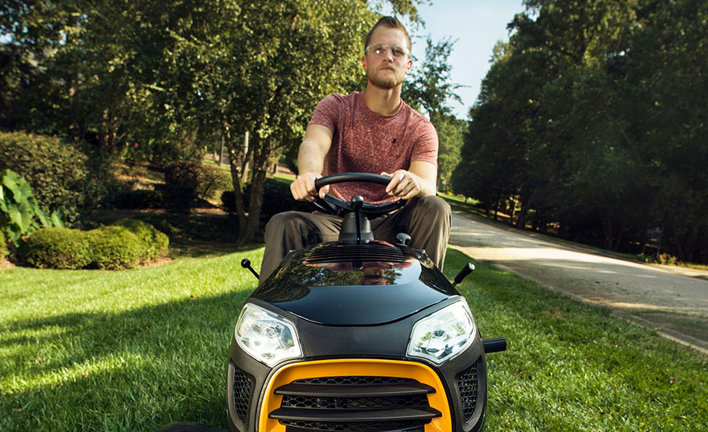 A man wears safety goggles to use his riding mower.
