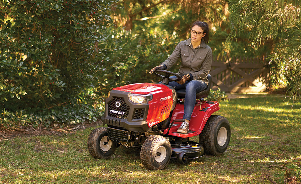 Woman on a riding lawn mower.