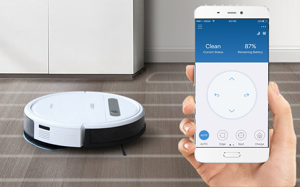 A hand holding a smartphone in front of a robot vacuum on hardwood flooring