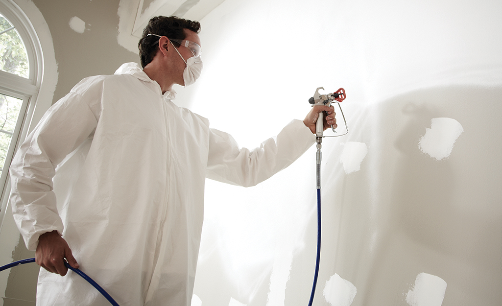A person in protective paint gear using a paint sprayer.