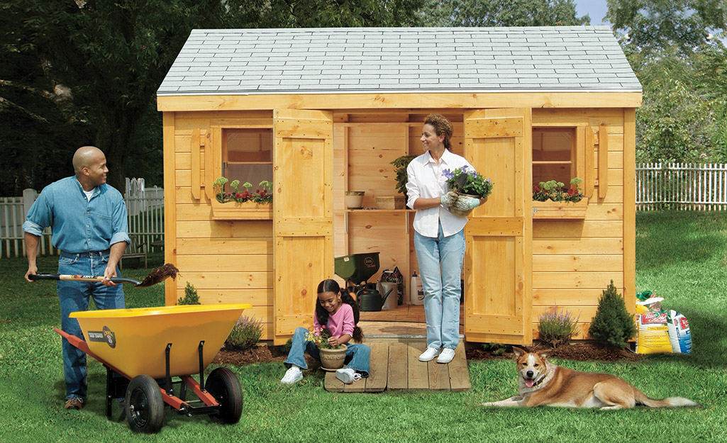 A family gardening outside a garden shed.