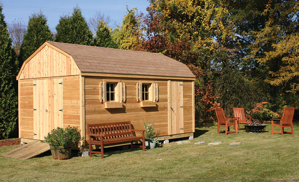 A wood shed with a nearby fire pit and seating area.