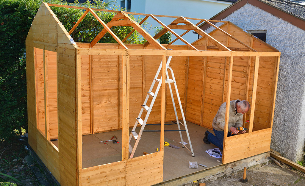A man building the walls of a wood shed.