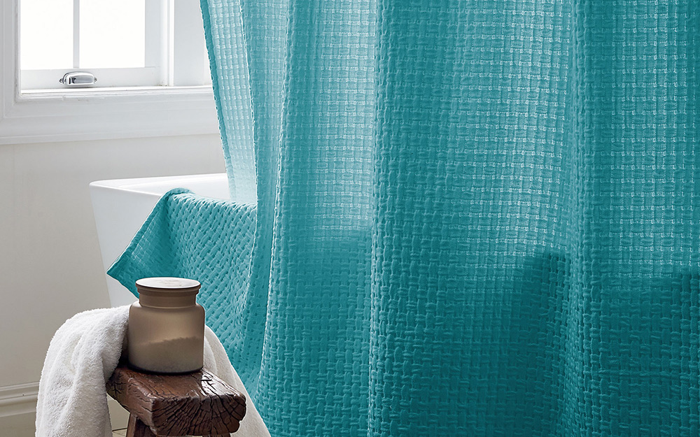 a teal shower curtain hanging over a bathtub